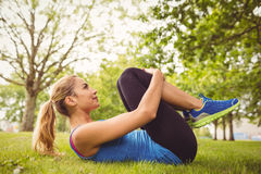 Woman doing stretching exercise while lying in grass Stock Photography