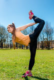 Woman doing stretching exercise outdoors Stock Photo