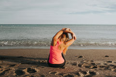 Woman doing stretching exercise at seashore. Stock Photos