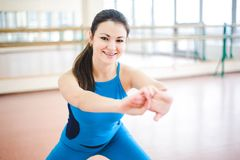 Woman doing stretching exercises on the floor at the gym stock photography