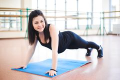 Woman doing stretching exercises on the floor at the gym. royalty free stock images