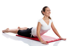Woman doing stretching exercises. On a mat shot in the studio Stock Images