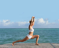 Woman doing stretching exercises on the shore Royalty Free Stock Photos