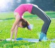 Woman doing stretching fitness exercise. Yoga postures. Beautiful sport woman doing stretching fitness exercise in city park at green grass. Yoga postures Royalty Free Stock Photography