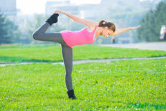Woman doing stretching fitness exercise. Yoga postures. Beautiful sport woman doing stretching fitness exercise in city park at green grass. Yoga postures Stock Photos