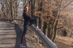 Woman doing stretching before jogging in forest stock image