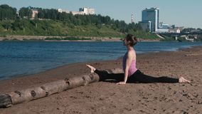 Woman doing stretching sitting on twine in the sandy beach at sunset. Beautiful city view. stock footage