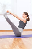 Woman doing stretching yoga exercise at sport gym Stock Photo