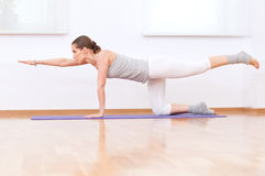 Woman doing stretching yoga exercise at sport gym Stock Images