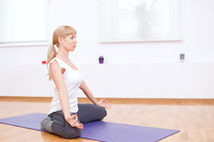 Woman doing stretching yoga exercise at sport gym Stock Photography