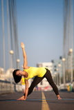 Woman doing stretching yoga exercises outdoors Stock Image