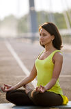 Woman doing stretching yoga exercises outdoors Stock Photos