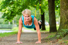 Woman doing suspension sling trainer sport Royalty Free Stock Photo