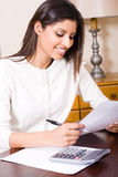 Woman doing taxes. A woman sitting at her desk at home doing the taxes Stock Image