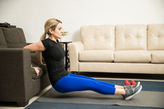 Woman doing tricep dips on a couch at home. Profile view of a pretty young woman doing tricep dips leaning on a couch in her living room Royalty Free Stock Image