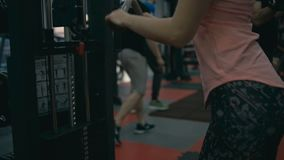 Woman doing triceps in gym machine. Shallow depth of field. Slow motion stock footage