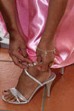 Woman Doing Up Shoe. A woman with brown skin doing up a silver shoe wearing a pink party dress Royalty Free Stock Photos