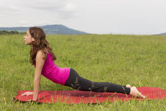 Woman doing upward facing dog in yoga outdoors Stock Images