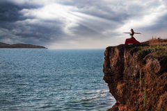 Woman doing virabhadrasana warrior yoga pose. Beautiful woman doing virabhadrasana warrior yoga pose on the cliff near the ocean with dramatic sky at background royalty free stock photo
