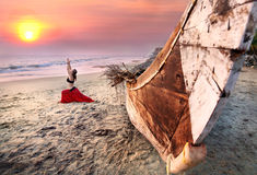 Woman doing virabhadrasana warrior yoga pose. Beautiful woman doing virabhadrasana warrior yoga pose on the beach near the ocean on sunset in India Stock Image