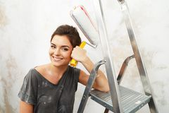 Woman doing wall painting Stock Image