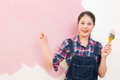 Woman doing wall painting and pointing Royalty Free Stock Photo