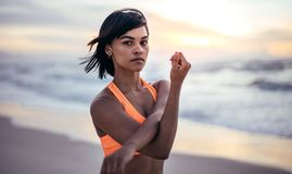 Woman doing warm up exercise at the beach. Determined woman stretching arms and exercising at the beach. Athlete doing warm up exercise at the sea shore Stock Image