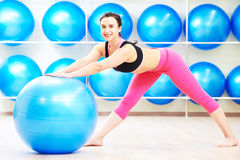 Woman doing warm up exercise with fitness ball Royalty Free Stock Photography