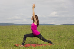 Woman doing Warrior I pose outdoors during yoga Stock Photo