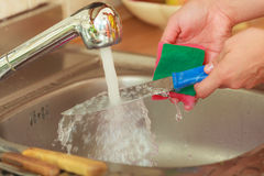 Woman doing the washing up in kitchen Royalty Free Stock Photo
