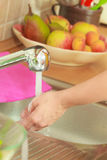 Woman doing the washing up in kitchen Stock Images