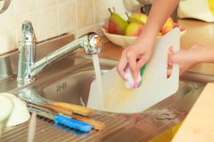 Woman doing the washing up in kitchen Stock Photo