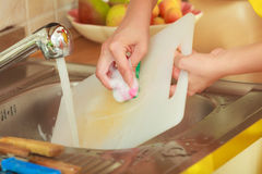 Woman doing the washing up in kitchen. Household. Closeup woman doing the washing up in kitchen cleaning plastic cutting board Stock Images