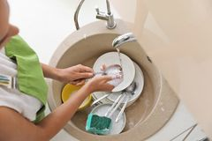 Woman doing washing up in kitchen sink. Cleaning chores stock images