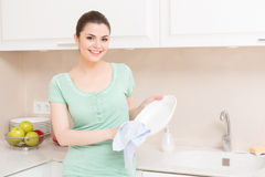 Woman doing washing up in kitchen Stock Photo