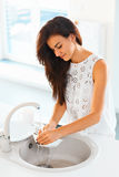 Woman doing the washing up in modern kitchen Stock Photography