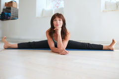 Woman doing wide angle seated forward bend yoga Royalty Free Stock Image