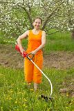 Woman doing work in her garden with grass-mower Stock Photography