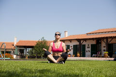 Woman doing yoga. Girl doing meditation on meadow against a house and the sky Stock Images