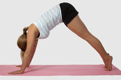 Woman doing yoga. Blond woman wearing exercise attire doing yoga stretch on pink mat over white Royalty Free Stock Photography