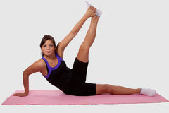 Woman doing yoga. Young brunette woman wearing workout clothes doing yoga stretch lifting leg on pink mat over white stock photos