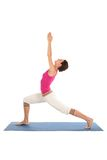 Woman doing yoga. Woman Posing On A Blue Yoga Mat Royalty Free Stock Images