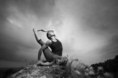 Woman doing yoga against the setting sun Stock Image