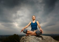 Woman doing yoga against the setting sun Stock Photography