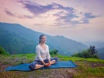 Woman doing yoga asana Baddha Konasana outdoors. Sporty fit woman practices yoga asana Baddha Konasana - bound angle pose outdoors in HImalayas mountains on Royalty Free Stock Image