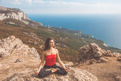 Woman doing yoga asana in mountains landscape Stock Images