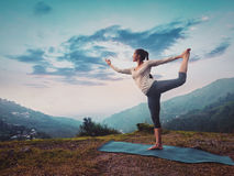 Woman doing yoga asana Natarajasana outdoors on sunset. Woman doing yoga asana Natarajasana - Lord of the dance pose outdoors on sunset in Himalayas. Vintage stock image
