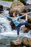 Woman doing yoga asana Natarajasana outdoors at waterfall Royalty Free Stock Photos