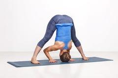 Woman doing yoga asana Prasarita padottanasana Royalty Free Stock Photos
