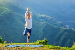 Woman doing yoga asana tree pose outdoors Stock Image
